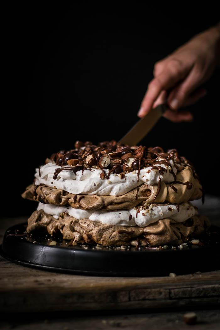 Beautiful layers of crispy and chewy meringue, decadent chocolate ganache and fluffy hazelnut whipped cream are what make this delicious chocolate hazelnut pavlova cake worth celebrating this blog's first birthday.