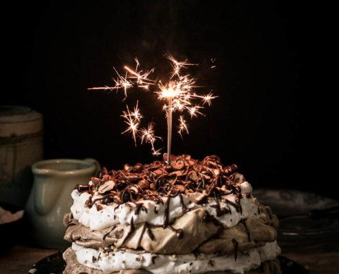 Beautiful layers of crispy and chewy meringue, decadent chocolate ganache and fluffy whipped hazelnut cream are what make this delicious chocolate hazelnut pavlova cake worth celebrating this blog's first birthday.