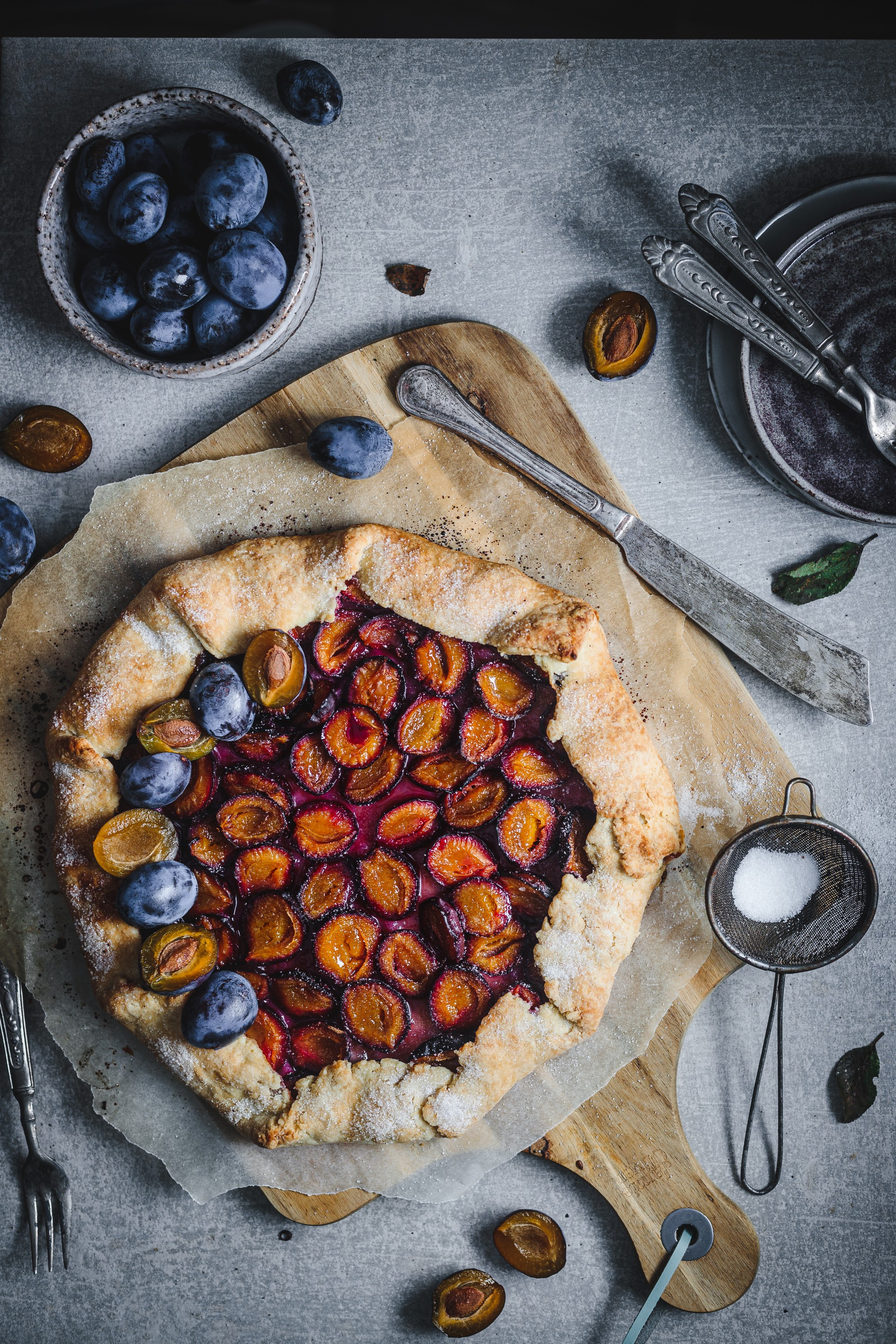 A plum pie on a wooden board on concrete backdrop with utensils