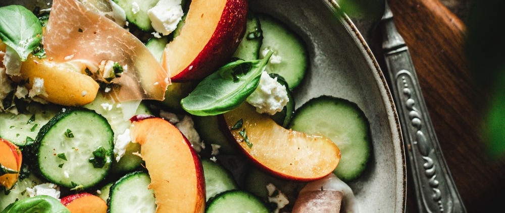 This refreshing Cucumber and peach salad is the perfect intro to Summer! With some prosciutto, feta cheese, and spicy basil dressing it's a winner!