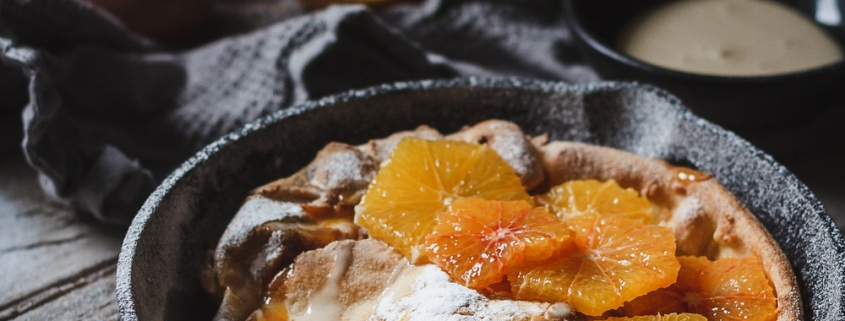 Orange Dutch baby. Light and airy topped with orange sauce, whipped honey and fresh oranges. It's made in no time! My favorite Winter breakfast lately because it's naturally sweet but also fresh at the same time.