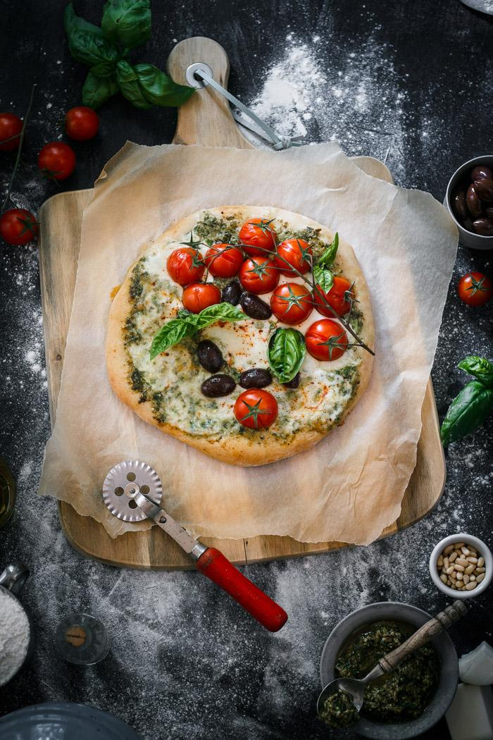 Italian flavors with a twist in one delicious spicy goat cheese pesto pizza loaded with fresh cherry tomatoes, mozzarella and black olives. I could eat this pizza every day!
