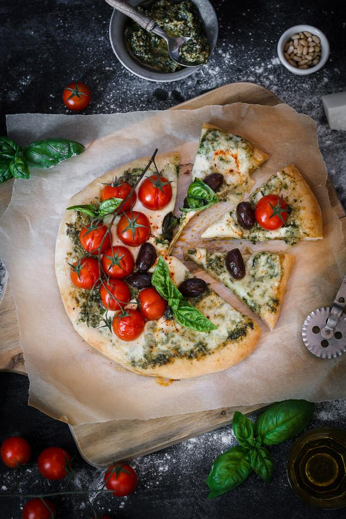 Italian flavors with a twist in one delicious spicy goat cheese pesto pizza loaded with fresh cherry tomatoes, mozarella and black olives. I could eat this pizza every day!